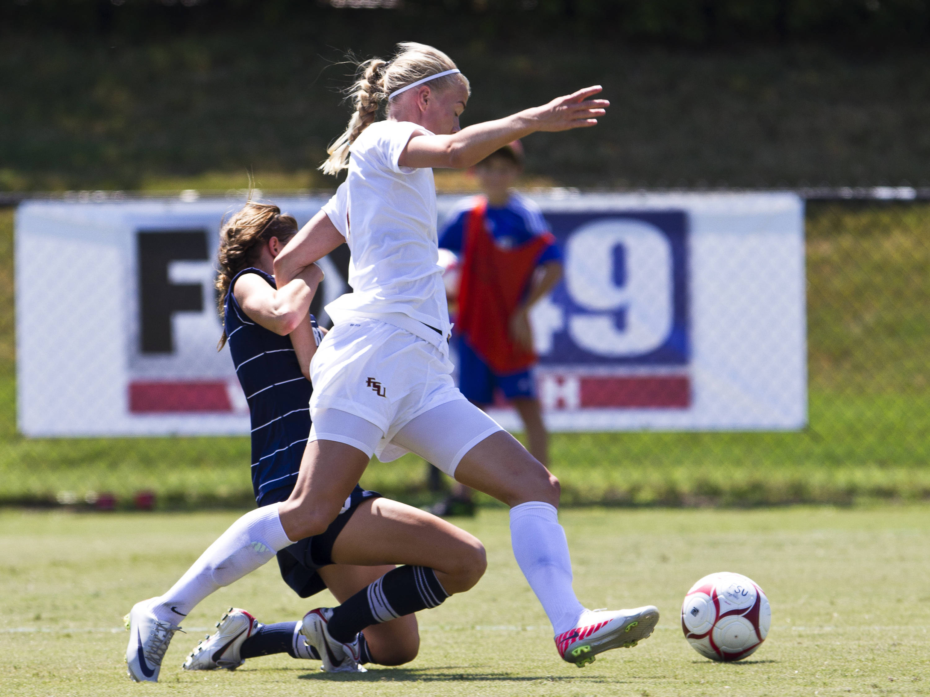 Dagny Brynjarsdottir (7) carries the ball downfield as a defender from North Florida attempts to tackle her from behind.
